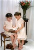 stock photo of fancy-dress  - Soft focus portrait of two young sisters sharing a book - JPG