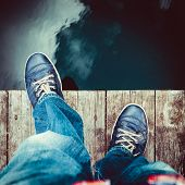 stock photo of tramp  - man on the pier takes a step into the water from above - JPG