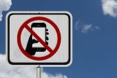 stock photo of traffic rules  - No Texting and Driving Sign White Information sign with symbol of a hand and texting with blue sky background - JPG