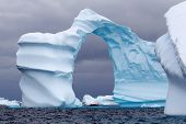 stock photo of iceberg  - Huge Arch Shaped Iceberg in Antarctic waters with a boat in the distance - JPG