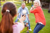 stock photo of baseball bat  - Grandparents Playing Baseball With Grandchildren In Park - JPG