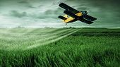 stock photo of propeller plane  - A crop dusting plane working over a field - JPG