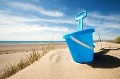 stock photo of spade  - Childs bucket and spade or sand pail and shovel at the beach on a sunny summer day - JPG