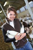 pic of dairy barn  - Smiling farmer holding bottles of goat milk in barn - JPG