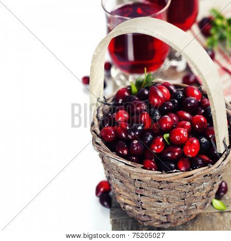 Ripe red cranberries in basket and juice on wooden background