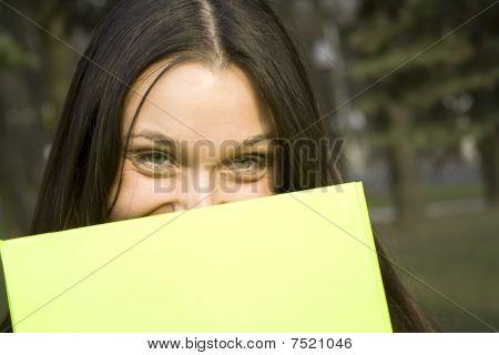 Female hiding behind a folder
