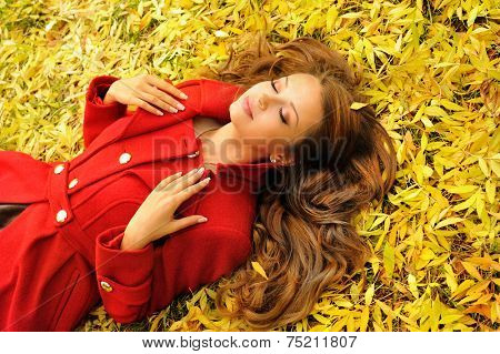 Attractive young woman in red coat lying in autumn leaves, outdoor.