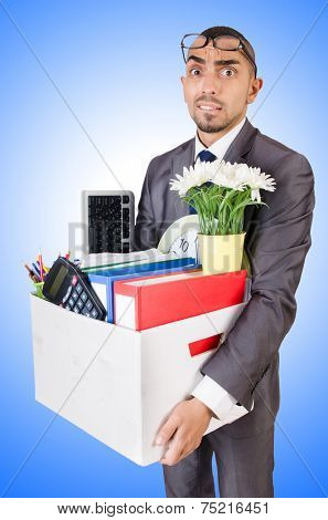 Man being fired with box of personal stuff