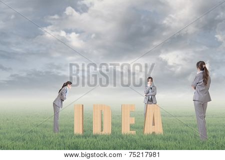 Concept of strategy, plan, idea etc with 3d wooden text and businesswoman under copyspace sky. The Asian woman is the same one.