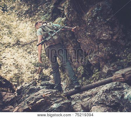 Man hiker walking across stream in mountain forest