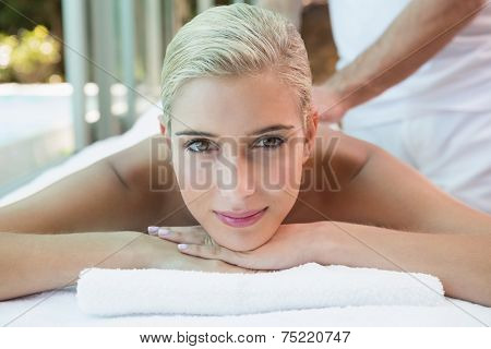 Close-up of a beautiful young woman receiving stone massage at health farm