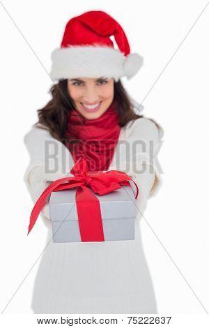 Festive brunette in santa hat giving gift on white background
