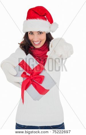 Excited brunette in santa hat giving gift on white background