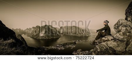 Man hiker looking at Reine village panorama, Norway