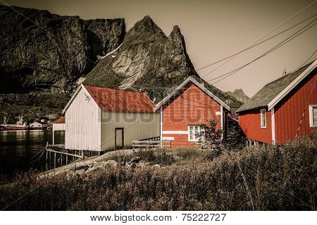 Traditional wooden houses against mountain peak in Reine village, Norway
