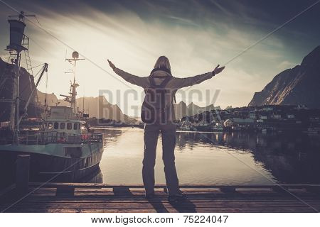Woman traveler looking at sunset in Reine village with arms wide open