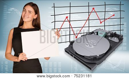 Smiling beautiful businesswoman in dress hold empty paper sheet. Open HDD are located near