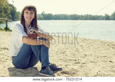 Young Woman Resting At The Beach With Old Camera.