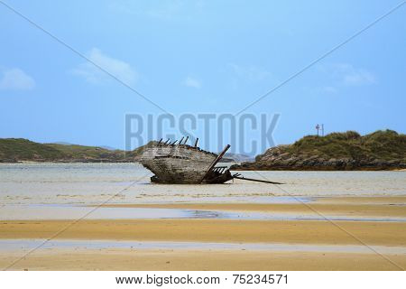 A wrecked boat languishes on a beach under a blue sky