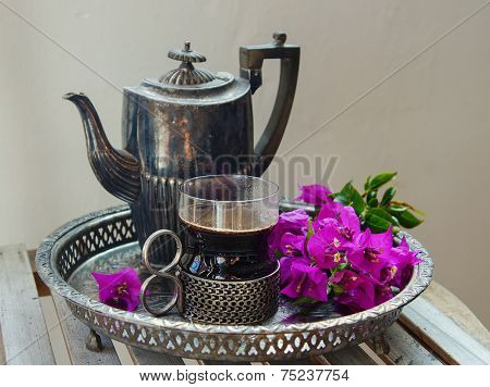 silver coffee pot with a cup of hot coffee and flowers