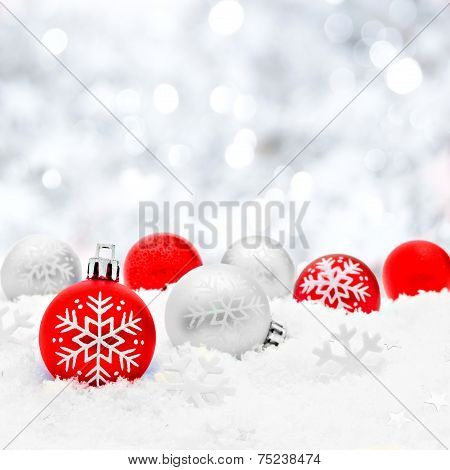 Christmas baubles in snow with silver background