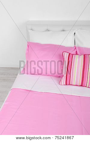 Bed in pink bed linen in room