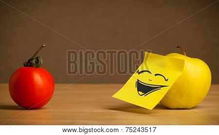 Apple with sticky post-it note gesturing to tomato