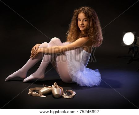 Pretty young ballet student sitting on floor, hugging legs, smiling, looking at camera, shoes lying next to her.