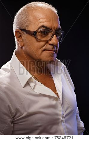 Portrait of casual old man in white shirt and glasses over black background. Side view.