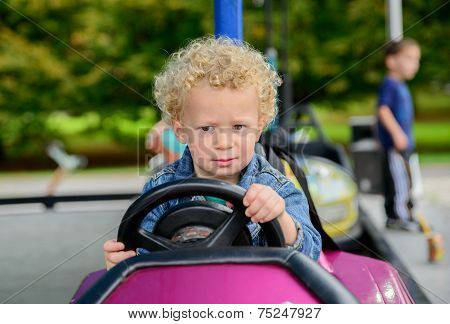 A Little Boy Driving A Bumper Car