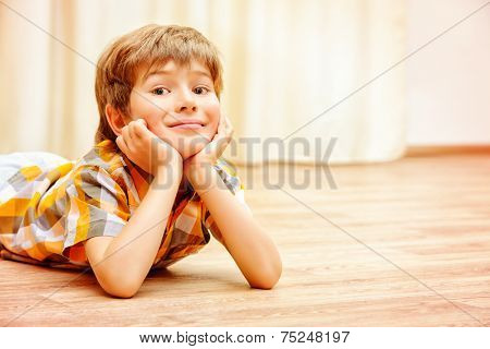 Happy smiling boy lying on a floor at home. Happy childhood.