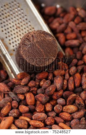 100% solid chocolate block on retro grater  on wood background and roasted cocoa beans