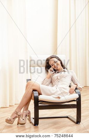 Beautiful happy young woman talking on the phone. She is at home in a comfortable chair.
