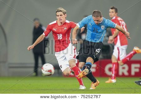 KLAGENFURT, AUSTRIA - MARCH 05, 2014: Christoph Leitgeb (#18 Austria) and Diego Perez (#15 Uruguay) fight for the ball in a friendly soccer game between Austria and Uruguay.