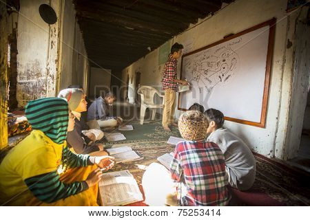 KATHMANDU, NEPAL - DEC 9, 2013: Unknown teacher and students in lesson at Jagadguru School. School established at 2013, to let new generation learn Sanskrit and preserve Hindu culture.