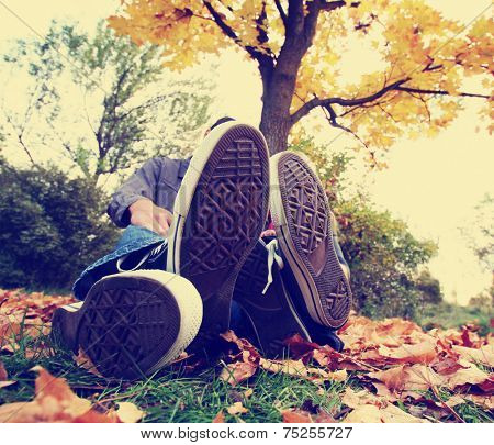 a family sitting under a tree with their feet in front toned with a retro vintage instagram filter