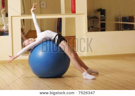 Little Gymnast Laying On Ball