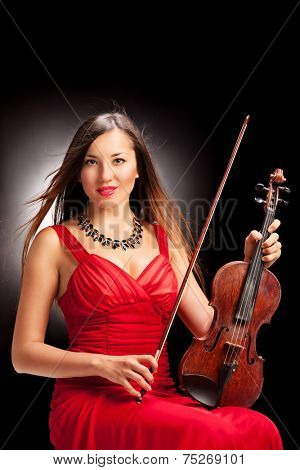 Vertical shot of a female violinist posing on black background