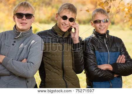 Three guys in autumn jacket and sunglasses, two of the boys twin brothers. Image with Instagram-like filter