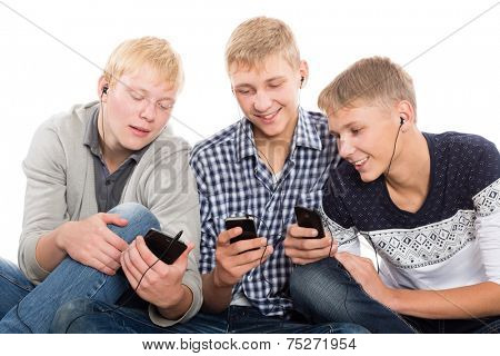 Friends use smartphones sitting on the carpet. Two of the boys twin brothers.