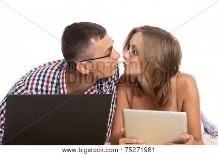 Enamoured young men kissing each other, holding laptop and Tablet PC