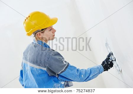 female plasterer at indoor wall renovation decoration with spatula and plaster