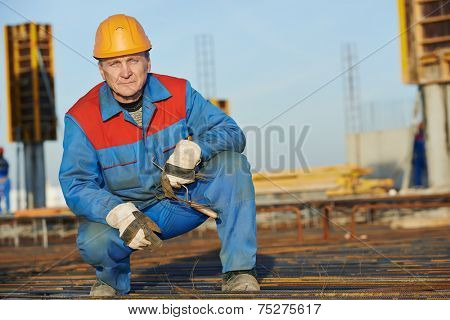 builder worker knitting metal rebar into framework reinforcement for concrete pouring at construction site