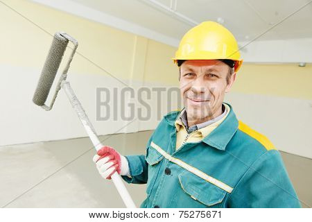 male plasterer portrait during floor covering works with self-levelling cement mortar