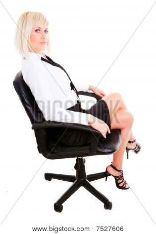 Blond Businesswoman Sitting On Chair Isolated Over White