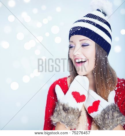 Beautiful happy young woman wearing winter hat and gloves covered with snow flakes. Christmas portrait concept.