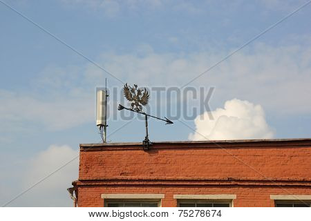 Metal Weather Vane On The Roof Of The Building