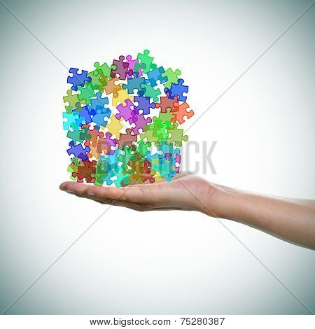 a man hand with a pile of puzzle pieces of different colors as the symbol for the autism awareness