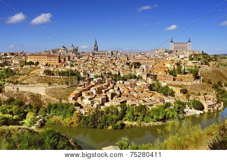 a panoramic view of Toledo, Spain, with the Tagus river in the foreground and the imposing Alcazar in the background