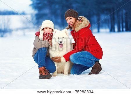 Christmas, Winter And People Concept - Beautiful Happy Family, Mother And Son Walking With White Sam